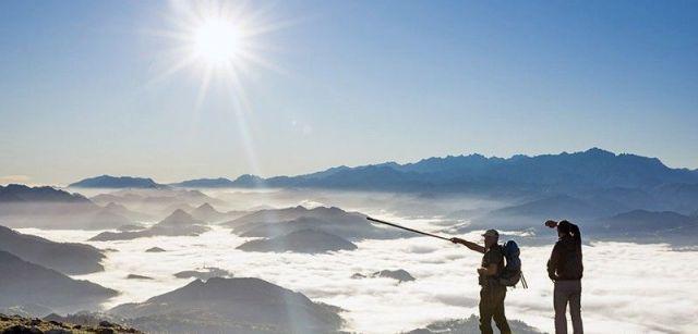 Un guarda de la reserva del Sueve (Asturias) señala el valle del río Sella cubierto por la niebla con los Picos de Europa al fondo / Foto: Roger Rovira