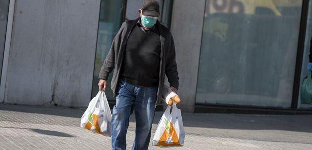 Un vecino confinado regresa de la compra protegiendo su boca y nariz con una mascarilla / Foto: Josep Cano