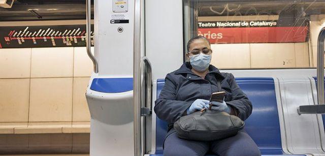 Una pasajera con máscara y guantes en un vagón semivacío del Metro de Barcelona / Foto: Josep Cano